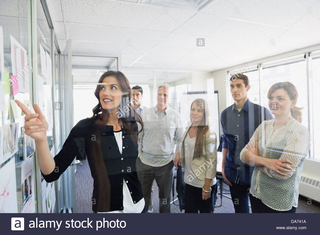 Businesswoman discussing project with colleagues in office - Stock Image