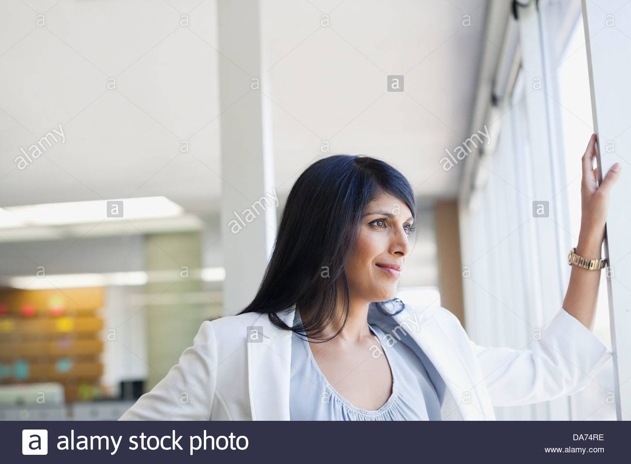Businesswoman looking out window in office - Stock Image