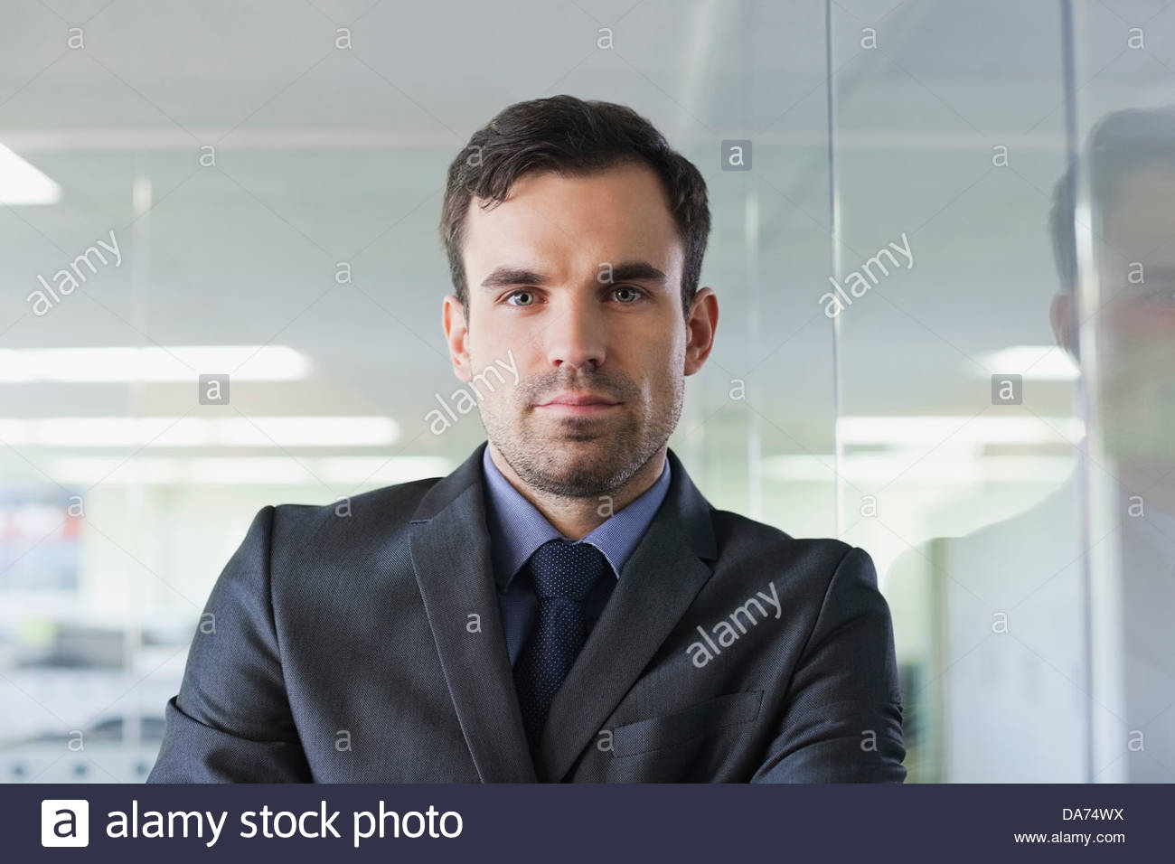 Portrait of businessman leaning on glass wall in office - Stock Image