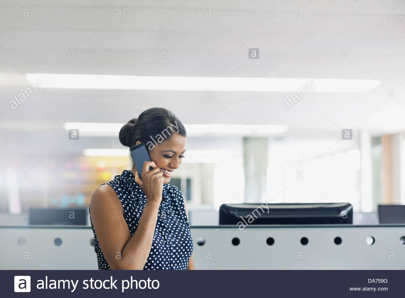 Businesswoman talking on mobile phone in office - Stock Image