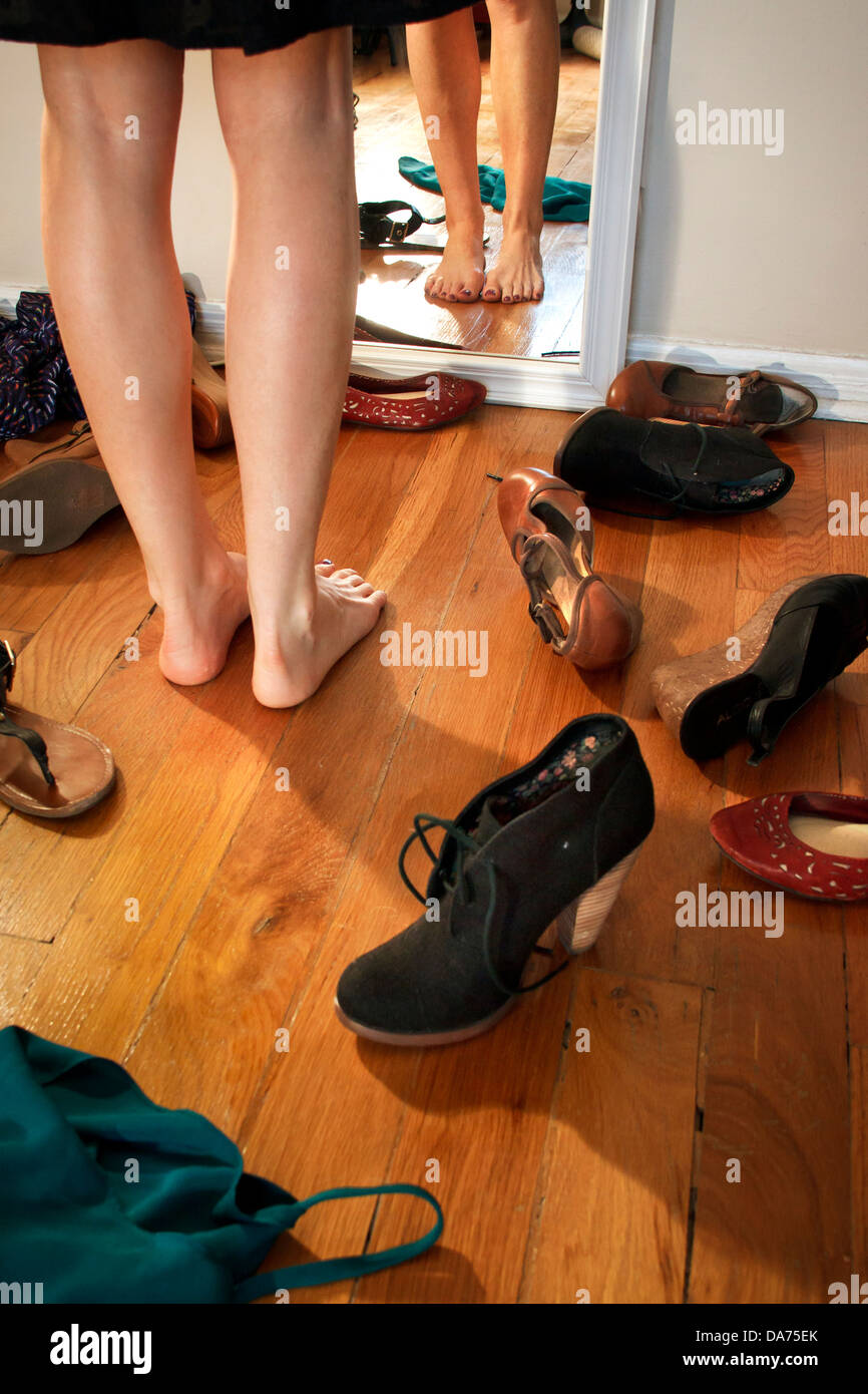Woman Decides What Shoes to Wear - Stock Image