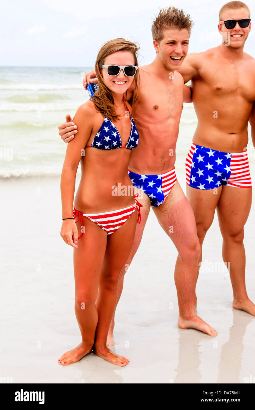 College guys and girls wear patriotic Stars and Stripes swimwear on July 4th in Florida - Stock Image