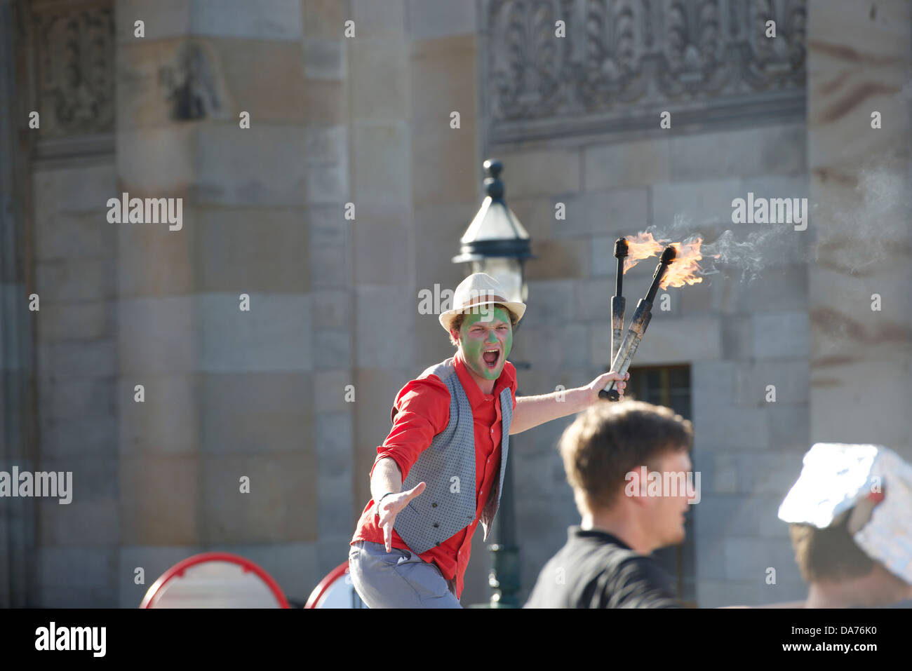 Juggler with fire-sticks entertains Festival visitors outside the Scottish National Gallery in Edinburgh. - Stock Image