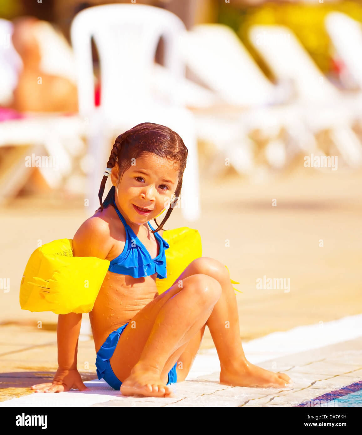 Cute little girl sitting near pool, active happy childhood, summer holidays, having fun outdoors, wearing swimwear Stock Photo