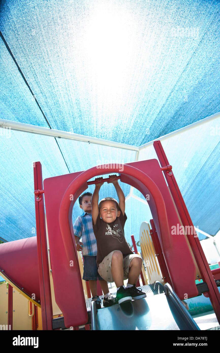 children playing on a playground slide hispanic asain caucasian Stock Photo