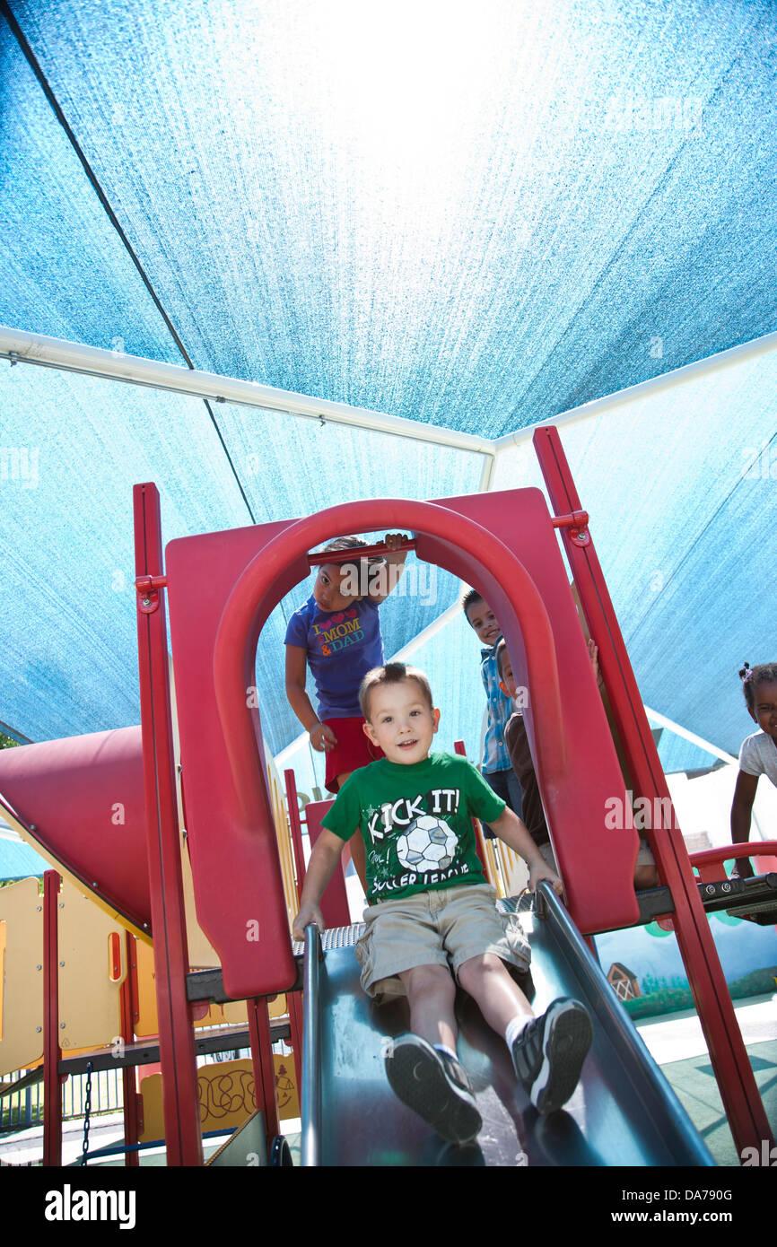 children playing on a playground slide hispanic asain caucasian - Stock Image