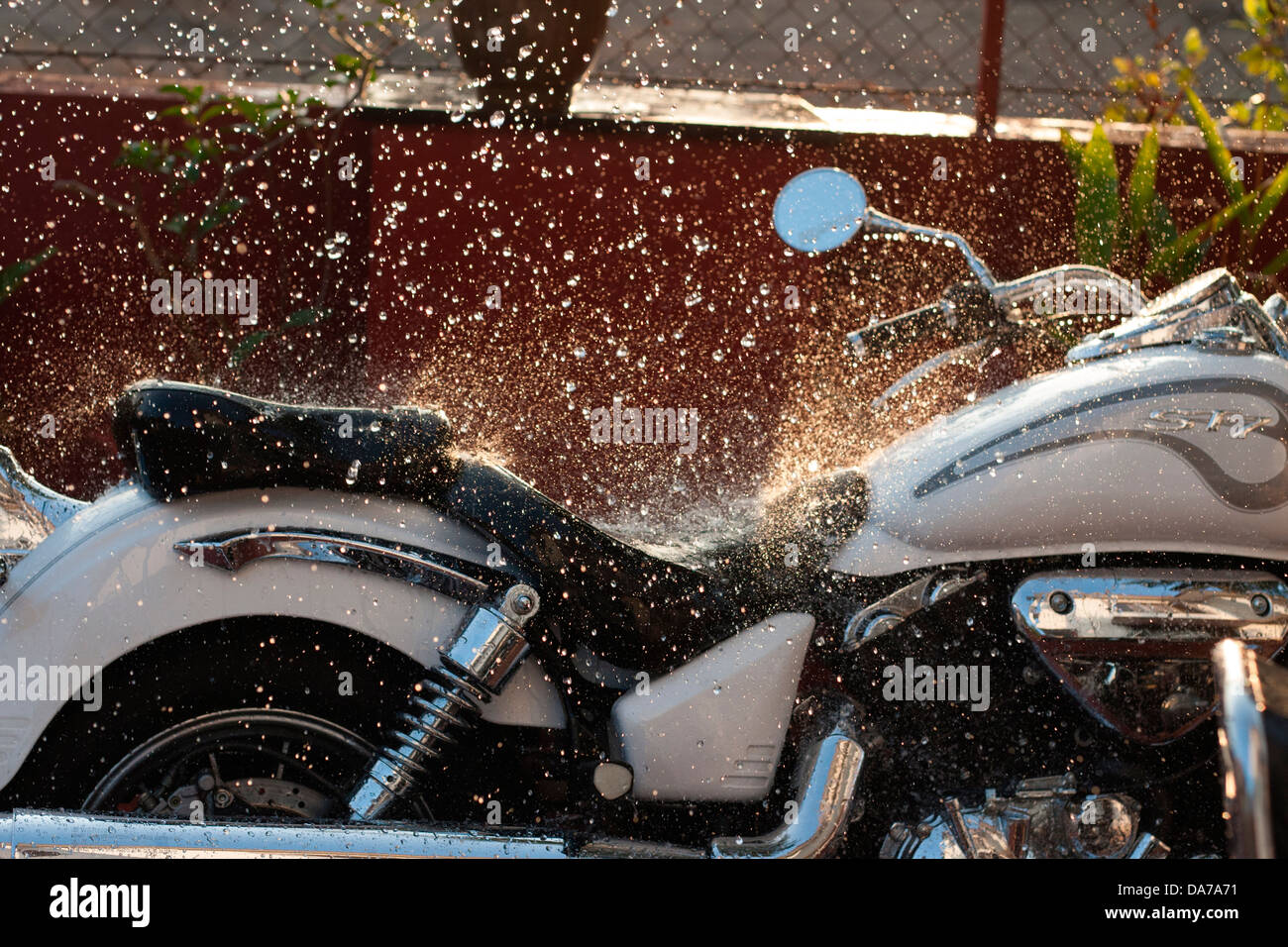 The Hyosung 700cc cruiser bike, one of the more affordable cruisers in India being cleaned and washed early morning - Stock Image