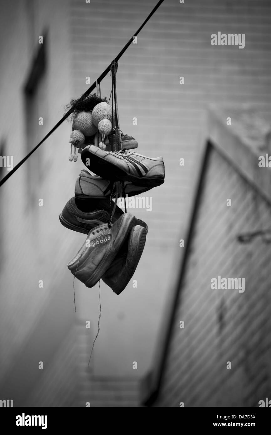 Sneakers hanging by the laces over powerlines - Stock Image