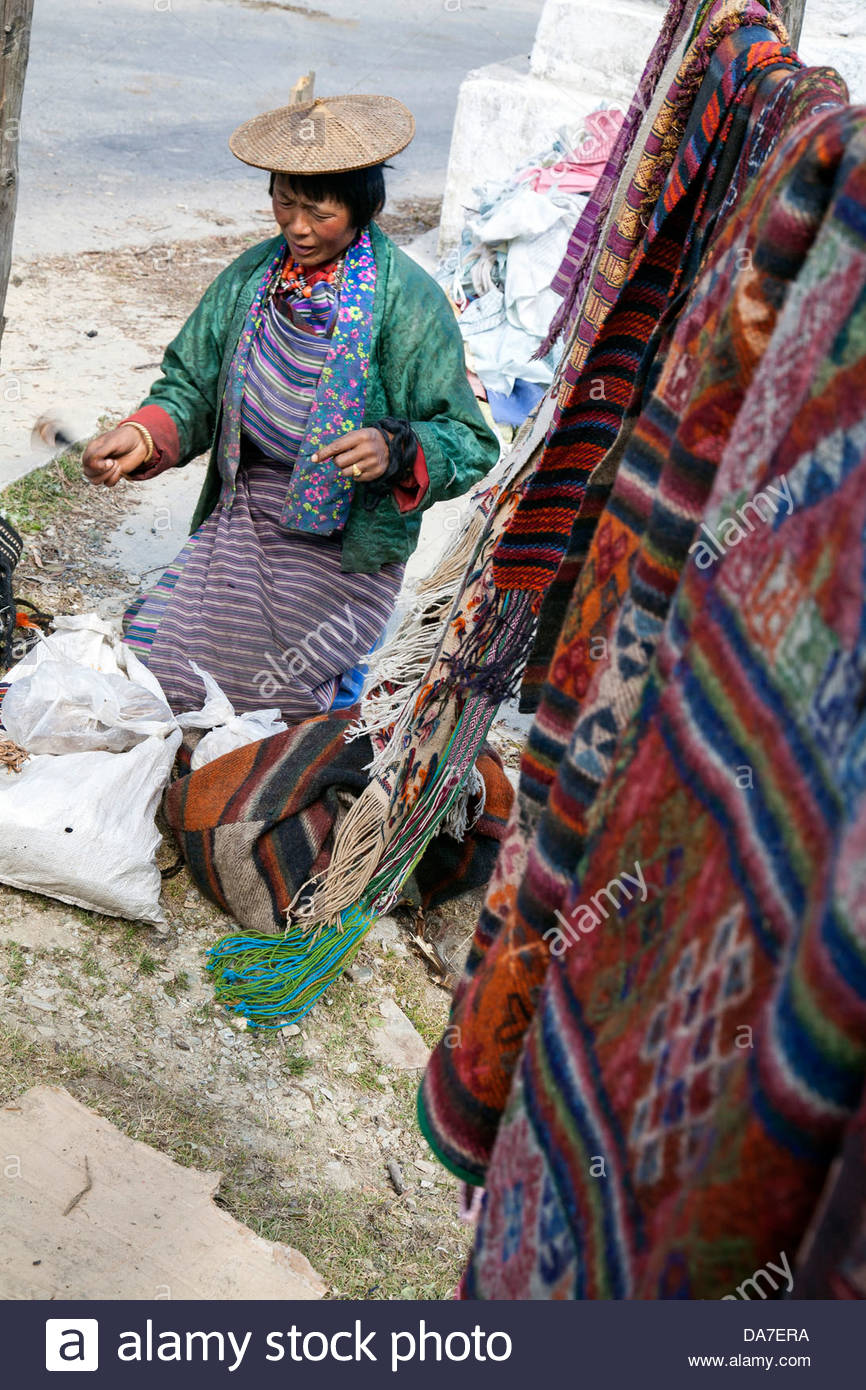 A woman spins yarn from yak wool. Bhutan. - Stock Image