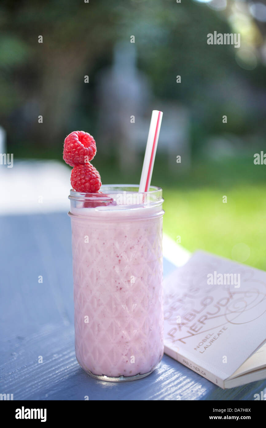 two raspberry smoothies outside on a sunny day - Stock Image