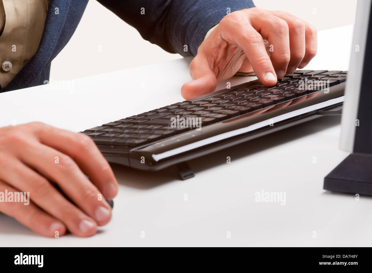 Businessman typing in a computer keyboard - Stock Image