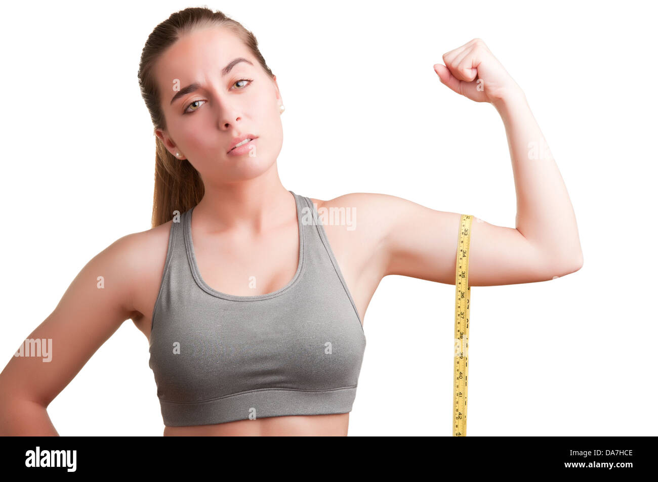 Powerful woman measuring her biceps with a yellow measuring tape - Stock Image