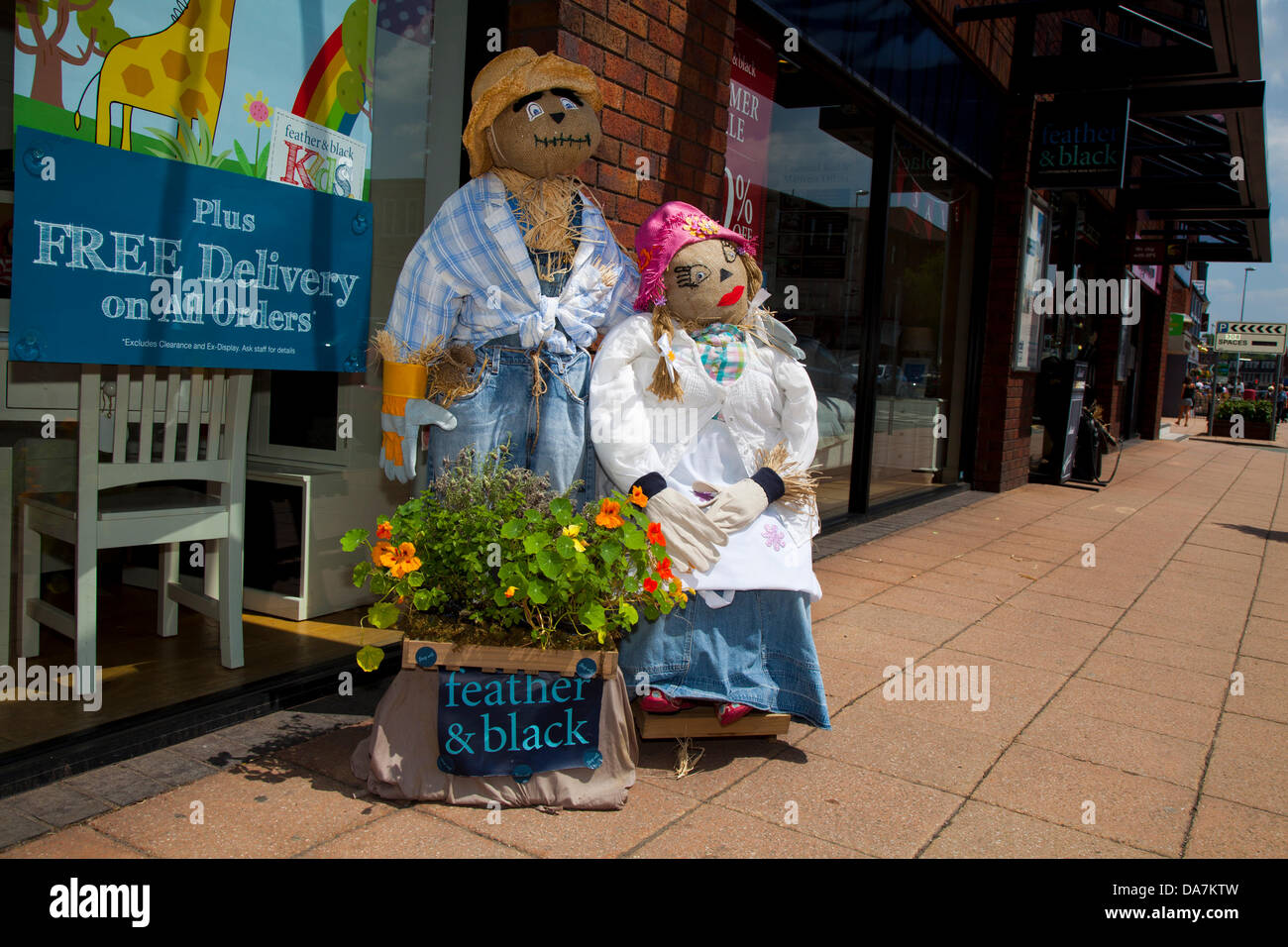 Furniture retailer Feather & Black store. Straw Man & woman advertising Free Delivery on all orders with - Stock Image