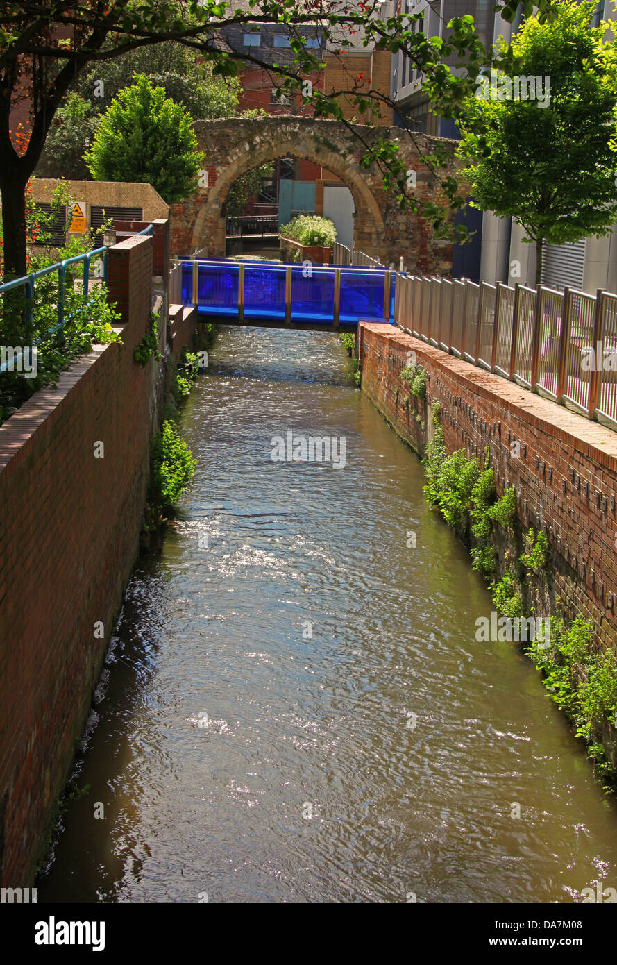 A Blue glass bridge spanning a brook in a historical area of town. - Stock Image