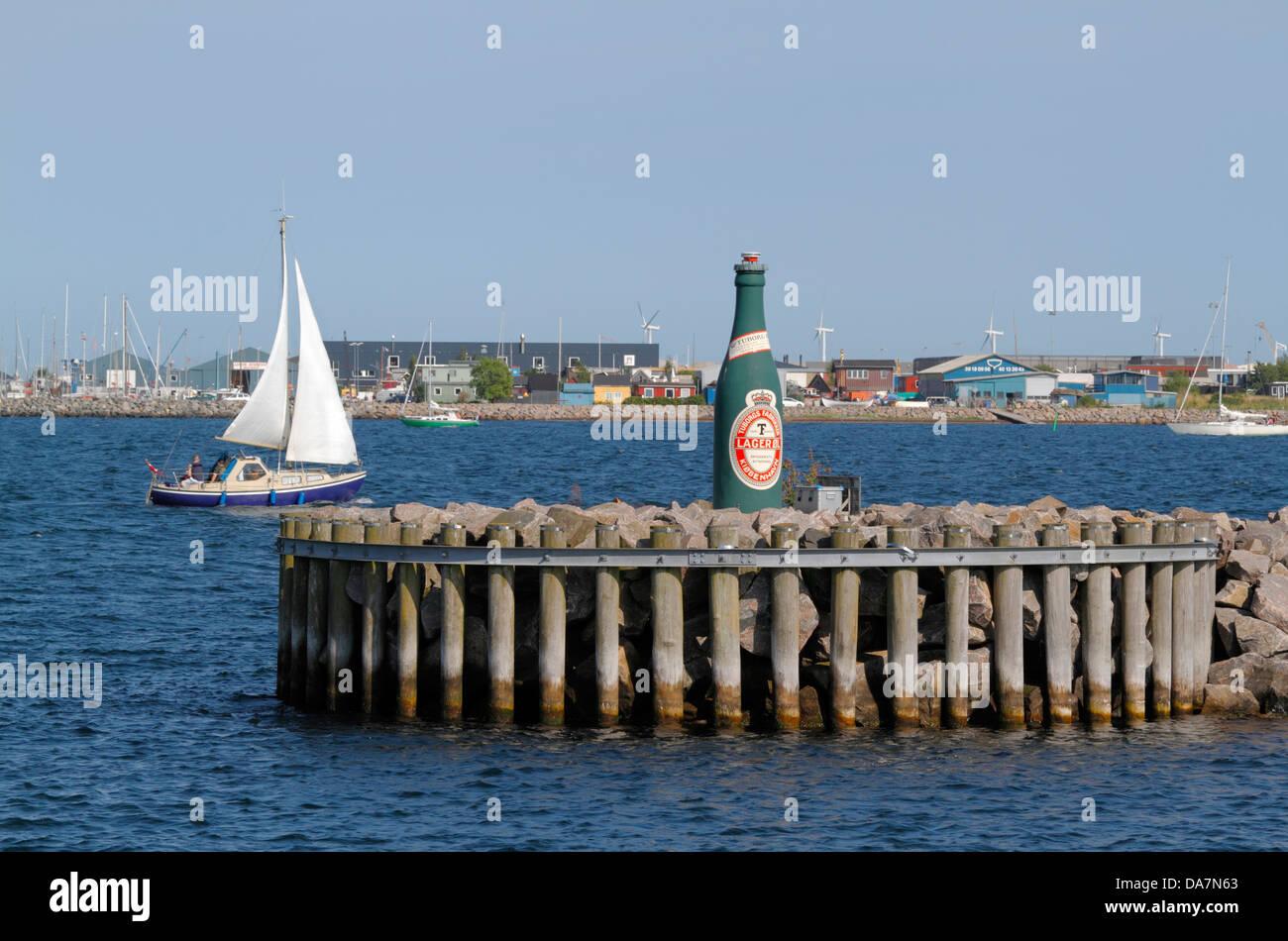A sailboat passing the port harbour light of Tuborg Harbour, a red labelled Tuborg bottle, Copenhagen North Harbour. - Stock Image