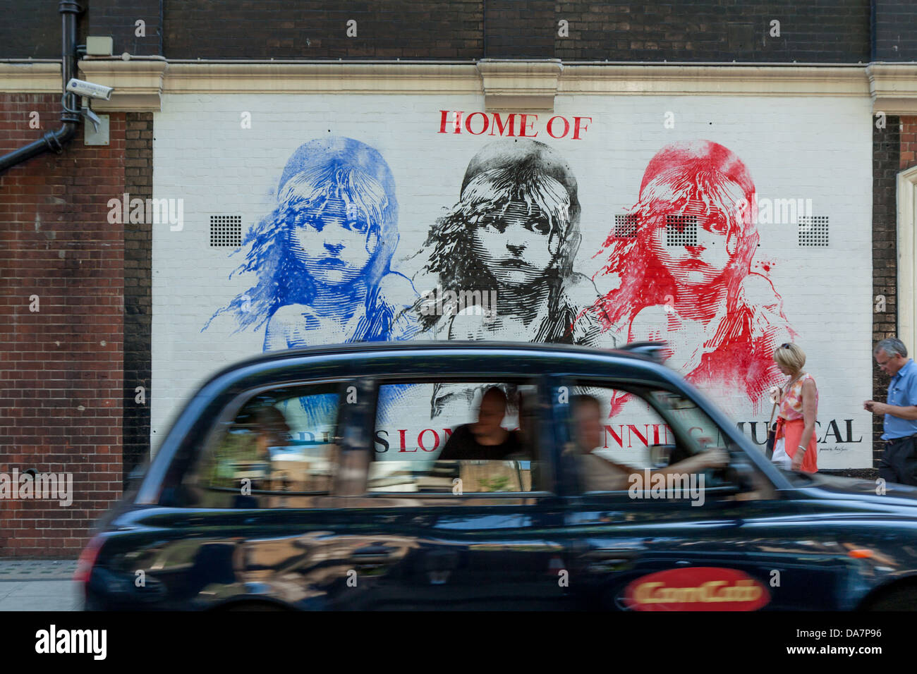 A black cab passes in front of a mural for Les Miserables in the West End - Stock Image