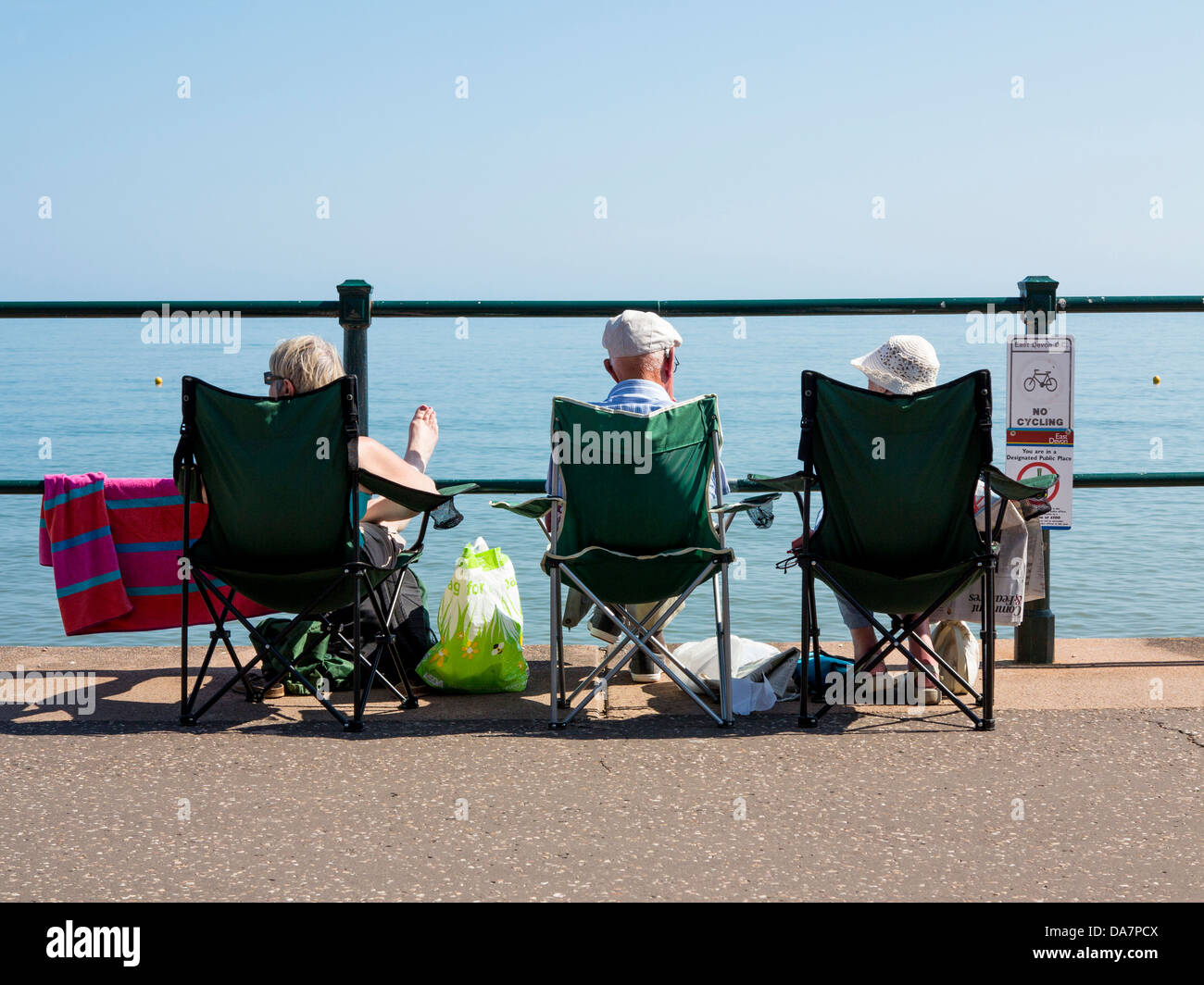Three elderly people in camping chairs sitting on the seafront at ...