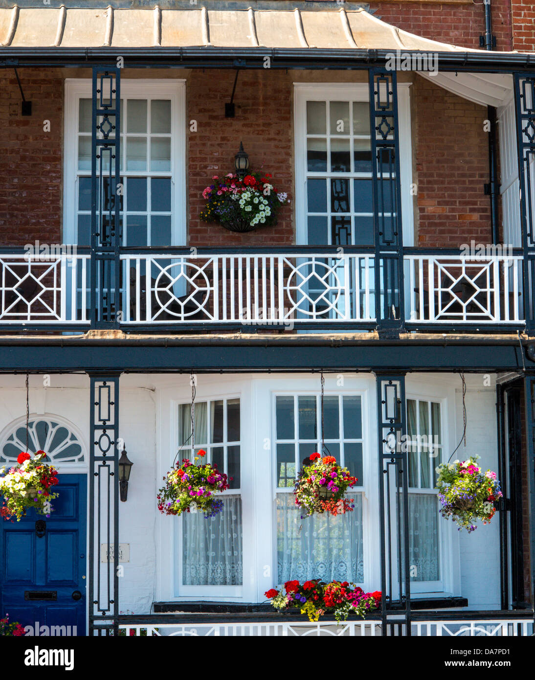 House with flower baskets and balconies on the seafront at Sidmouth, Devon, England - Stock Image