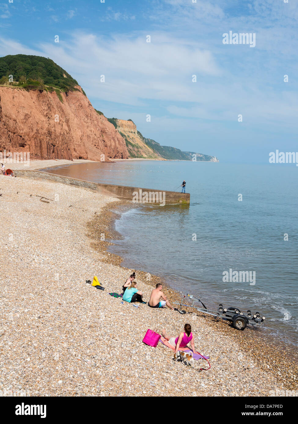 Sunbathers and fisherman at Sidmouth, Devon, England - Stock Image