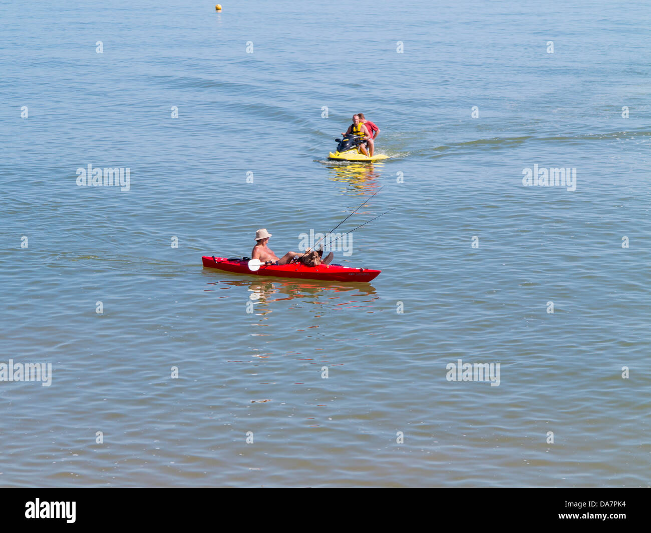 Canoeist and jet skier at Sidmouth, Devon, England - Stock Image