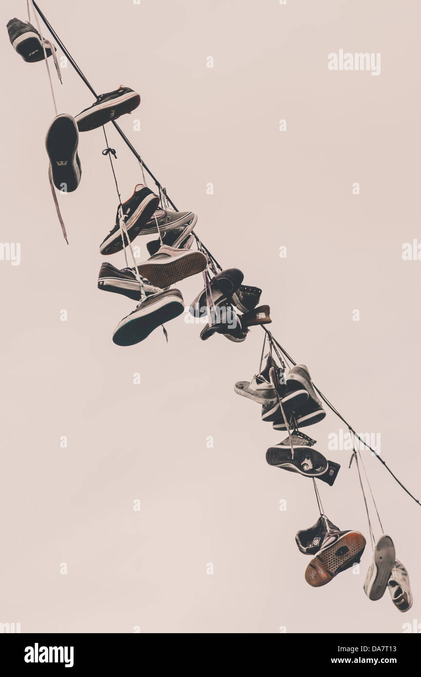 Running shoes hanging from a cable Stock Photo