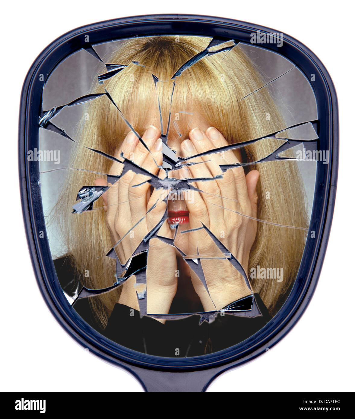 A woman covers her face reflected in a broken mirror or the shattered life concept - Stock Image