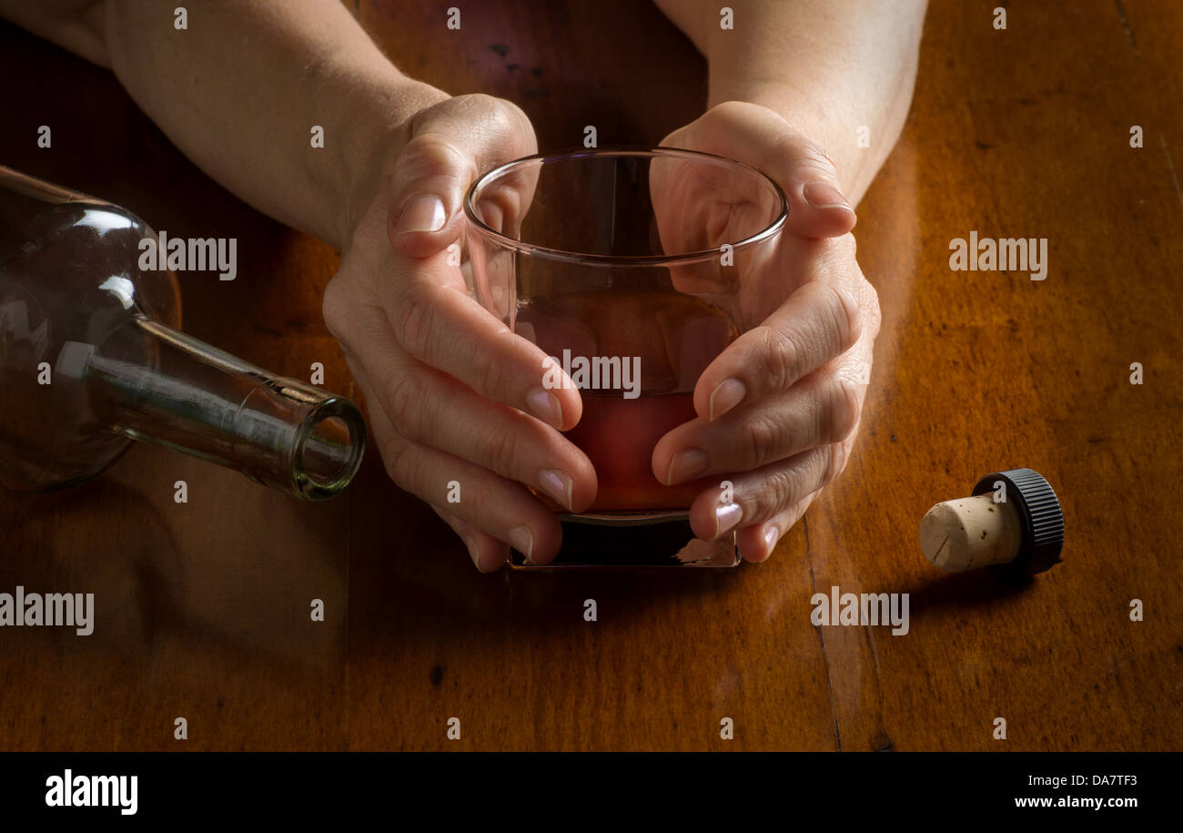 Concept photo closeup for alcoholism disease showing hands whiskey glass and empty bottle - Stock Image