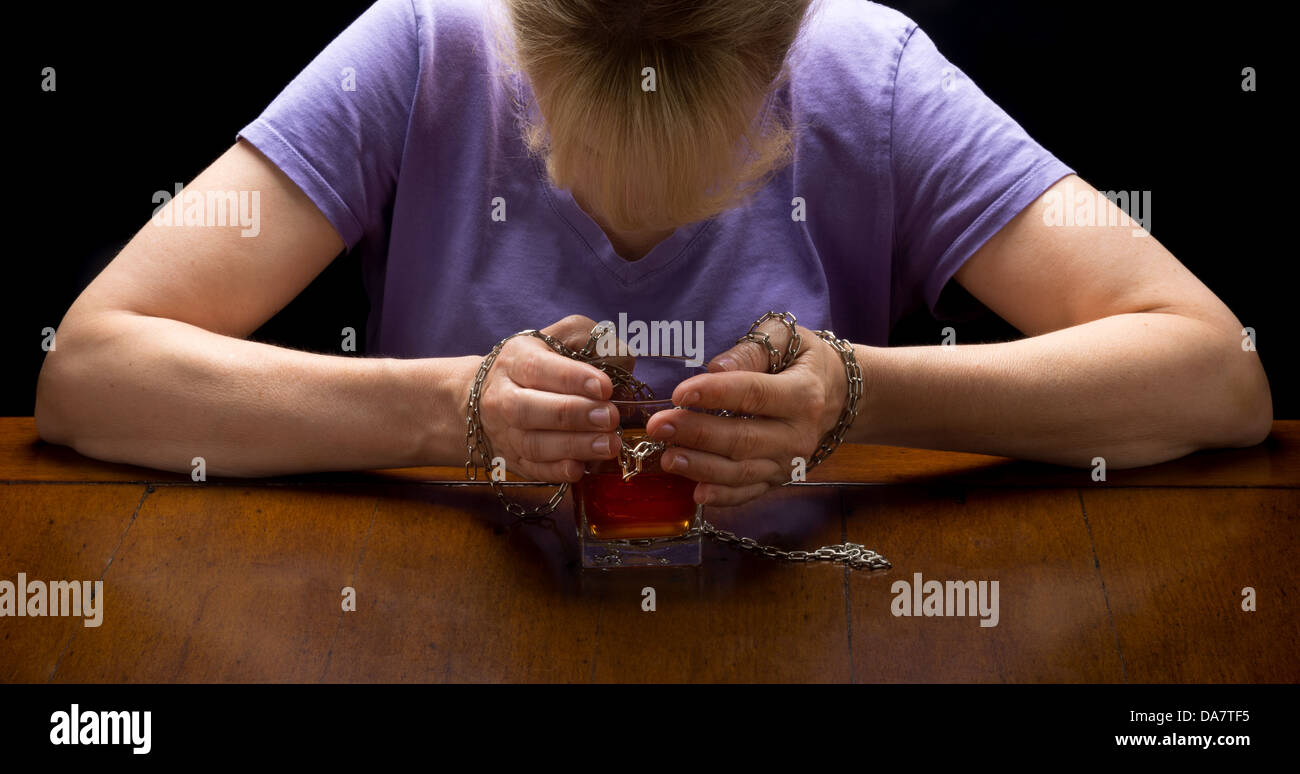 Concept photo closeup for alcoholism disease showing hands chained to whiskey glass with woman's head hovering - Stock Image