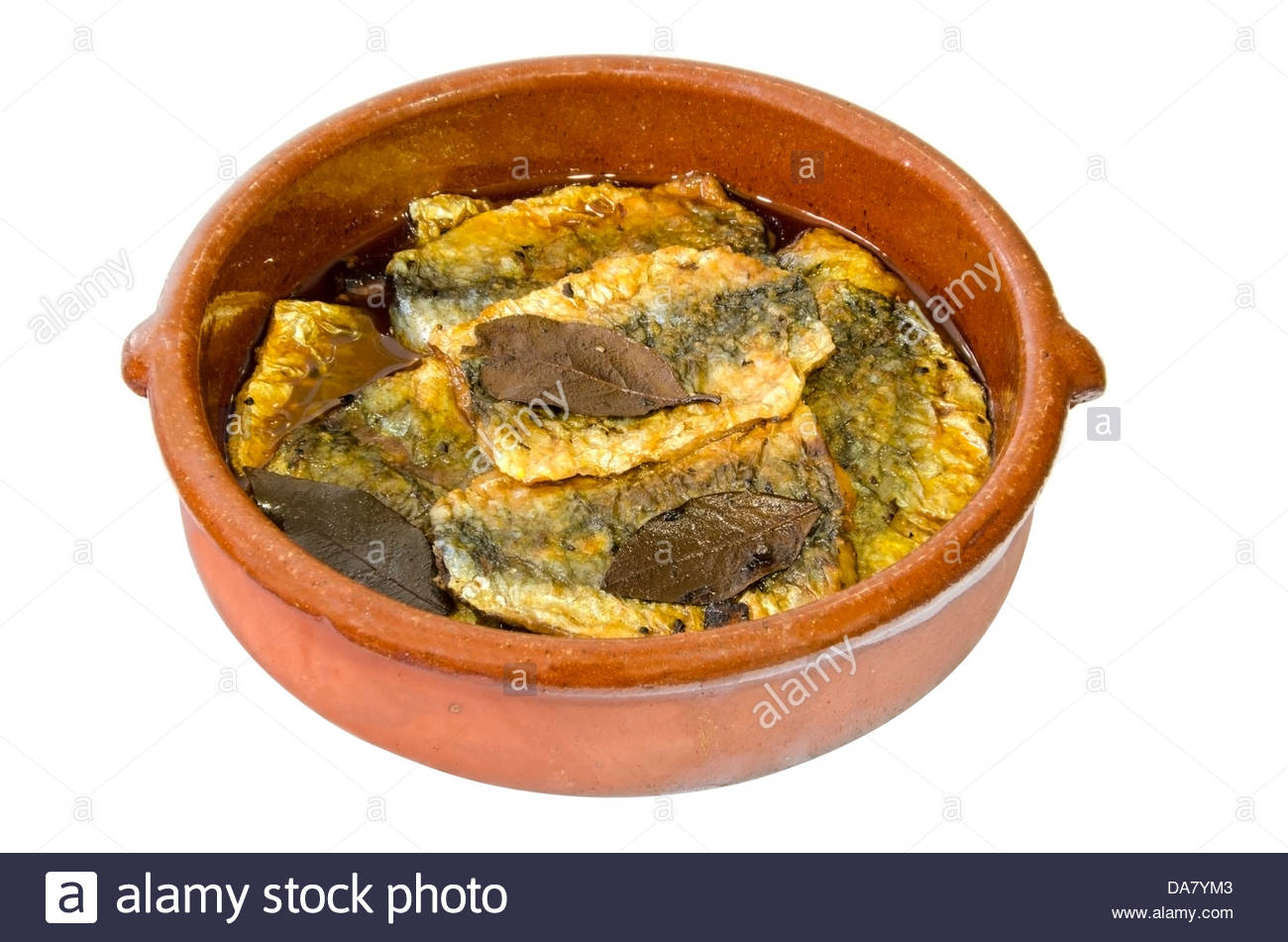 A clay plate of pickled sardines isolated over white - Stock Image
