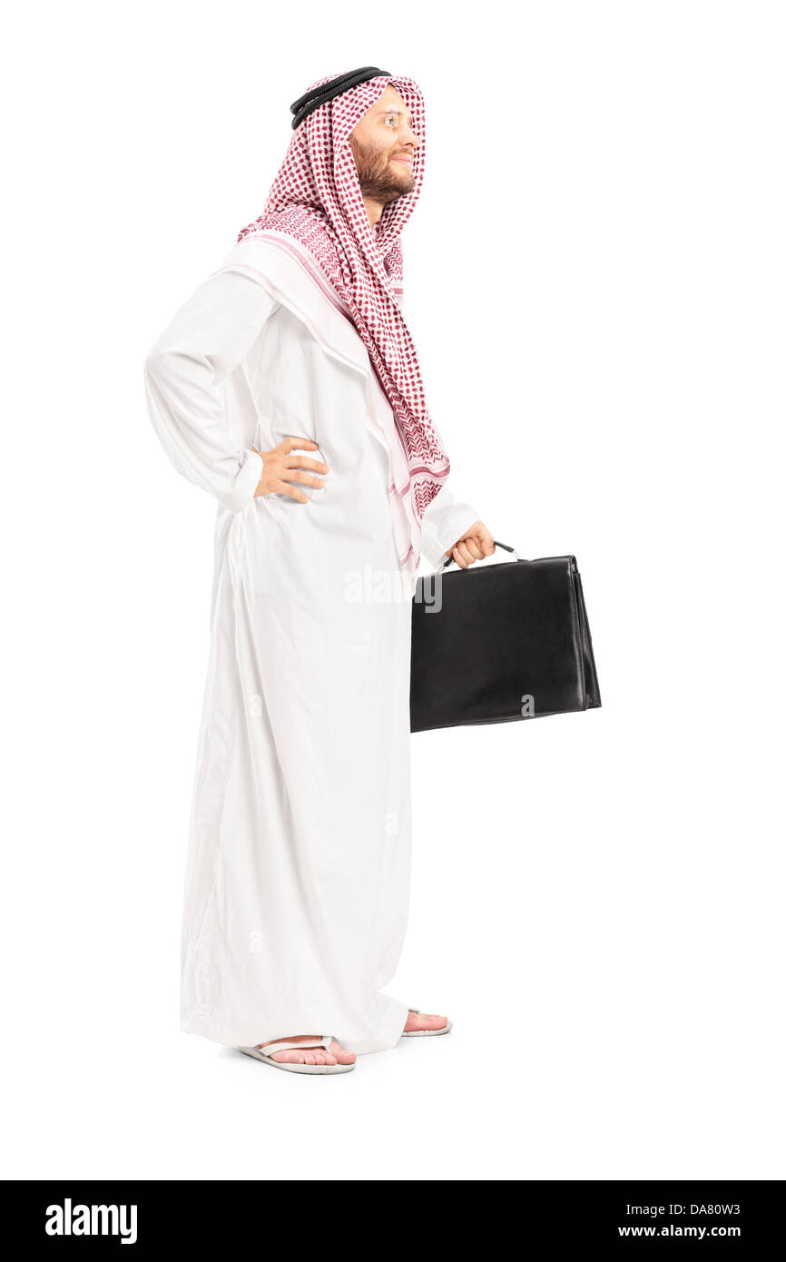 Full length portrait of a male arab person with suitcase posing - Stock Image