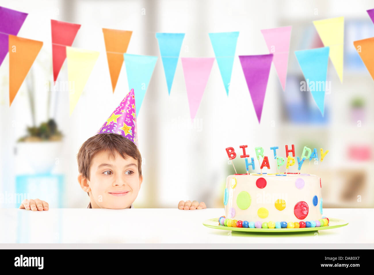 Smiling boy with party hat looking at a birthday cake - Stock Image