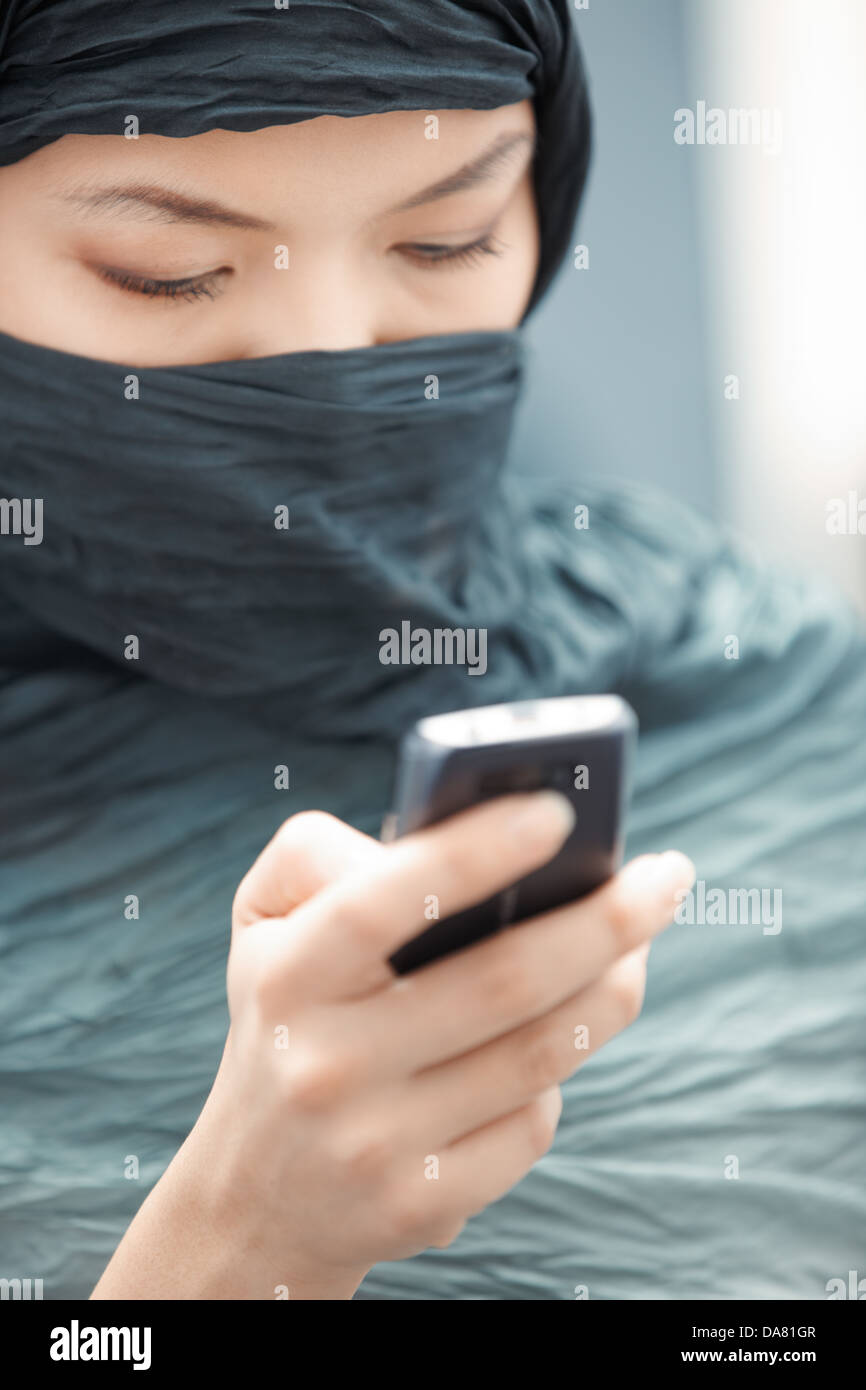 Oriental lady in hijab sending SMS via cell phone - Stock Image