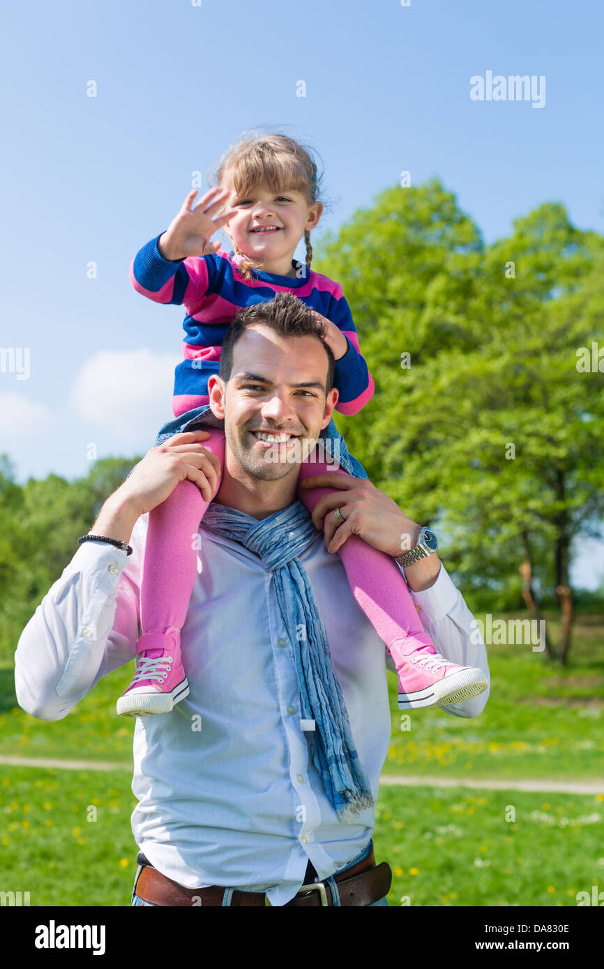 Father and daughter, he is carrying the girl on the shoulders and they do have lots of fun - Stock Image