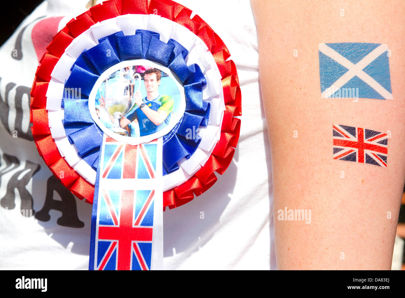 Wimbledon London UK. 7th July 2013. A tennis  fan wears a Rosette Ribbon to support Andy Murray  as he prepares - Stock Image