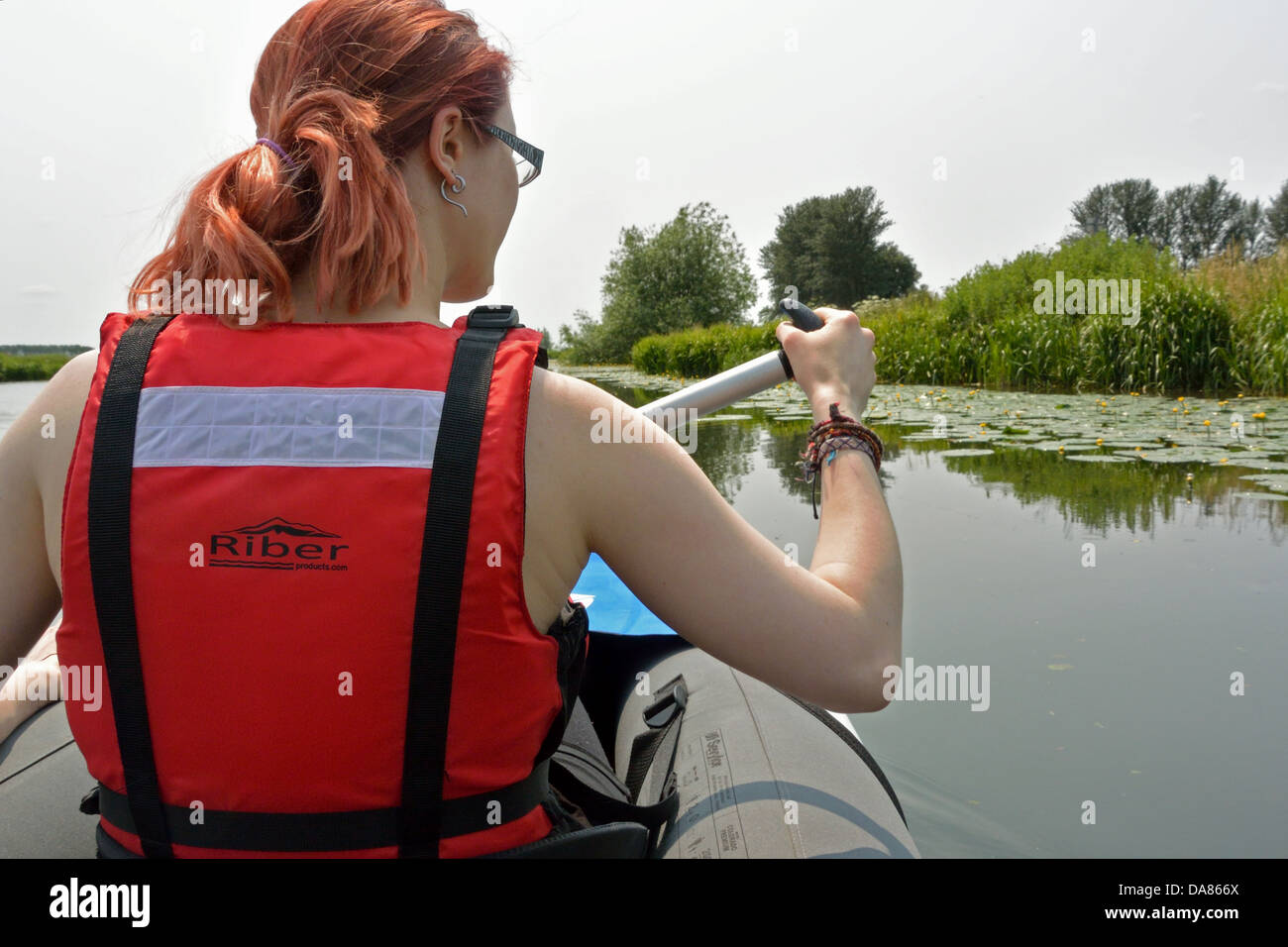 Young woman paddling a Sevylor Colorado Premium inflatable canoe on the River Great Ouse near Ely, Cambridgeshire, - Stock Image