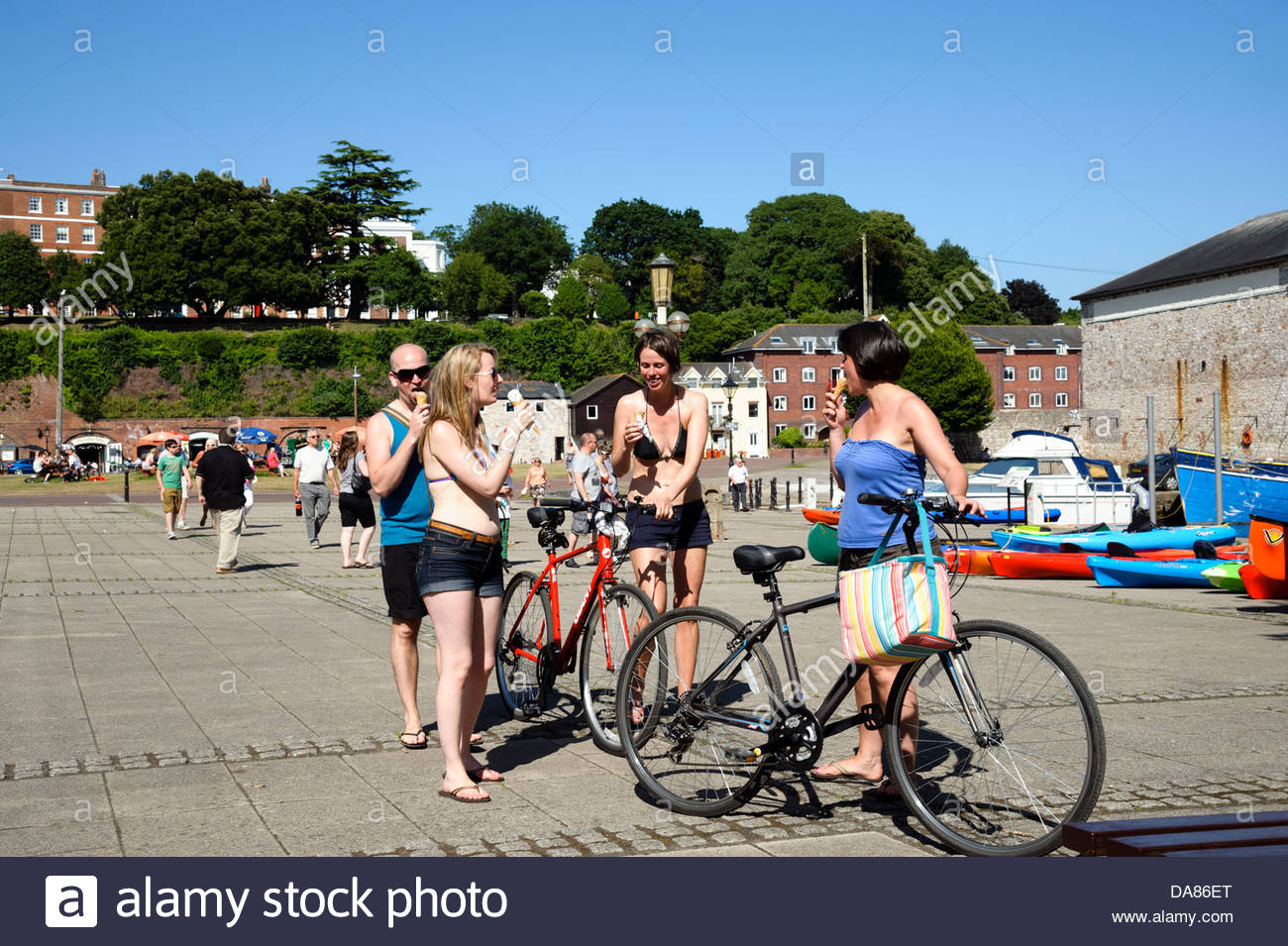 People enjoying ice creams on a summer day at The Quay, Exeter, Devon, UK. - Stock Image