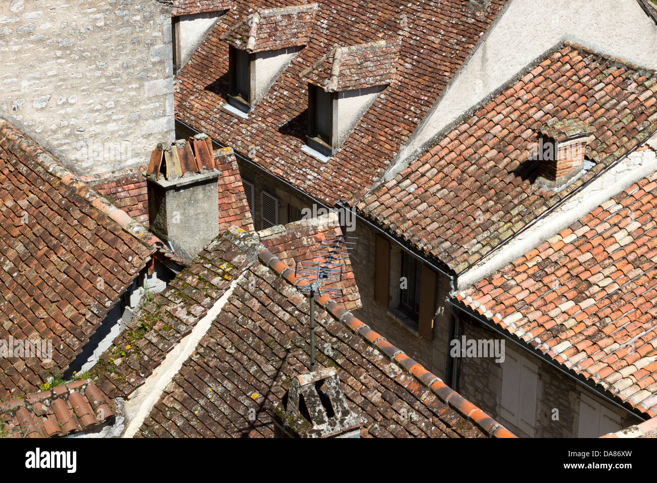 Red tile and stone roofs and chimneys in Rocamadour, France - Stock Image