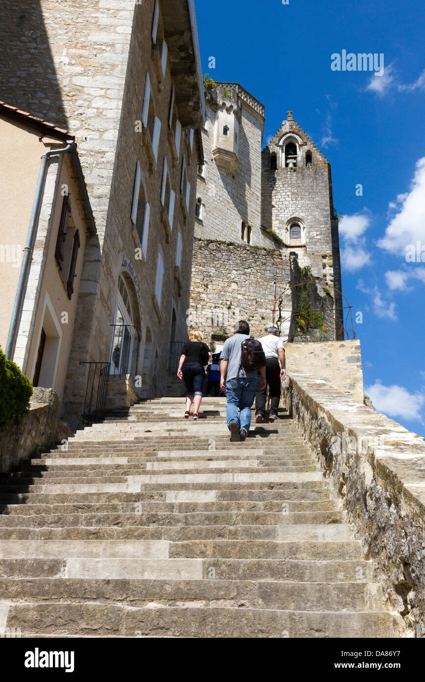 Tourists walking up steep steps toward historic churches and sanctuaries in Rocamadour, France - Stock Image