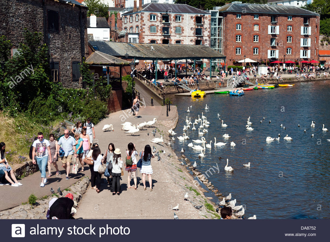 People enjoying a summer day on the riverbank at The Quay, Exeter, Devon, UK. - Stock Image