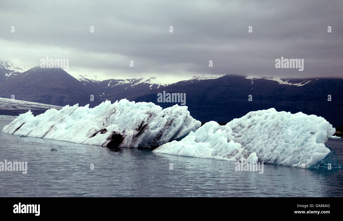 Icebergs seemingly sliced diagonally float seaward from Iceland's Jökulsárlón glacier lagoon - Stock Image