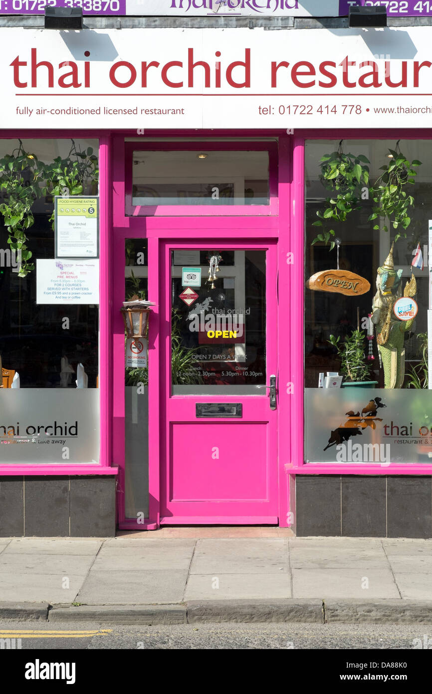 Bright pink door with open sign in window at the entrance to a UK Thai Restaurant & Bright pink door with open sign in window at the entrance to a UK ...