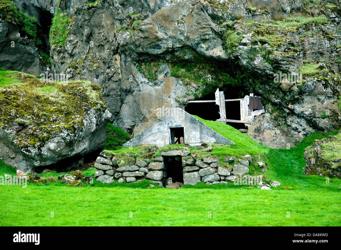 A roughly tended turf-roofed shelter and cave were once the dwellings of rural Icelanders - Stock Image