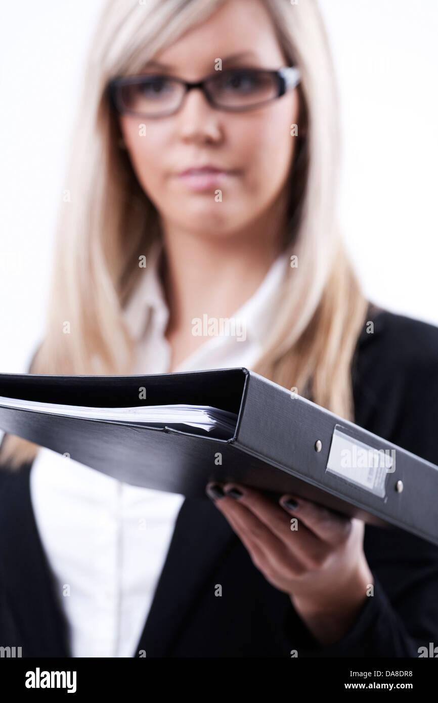 Young business women handing a folder (selective focus on folder) - Stock Image