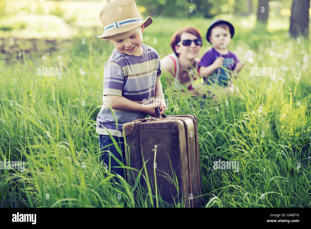 Cheerful family playing on green grass - Stock Image