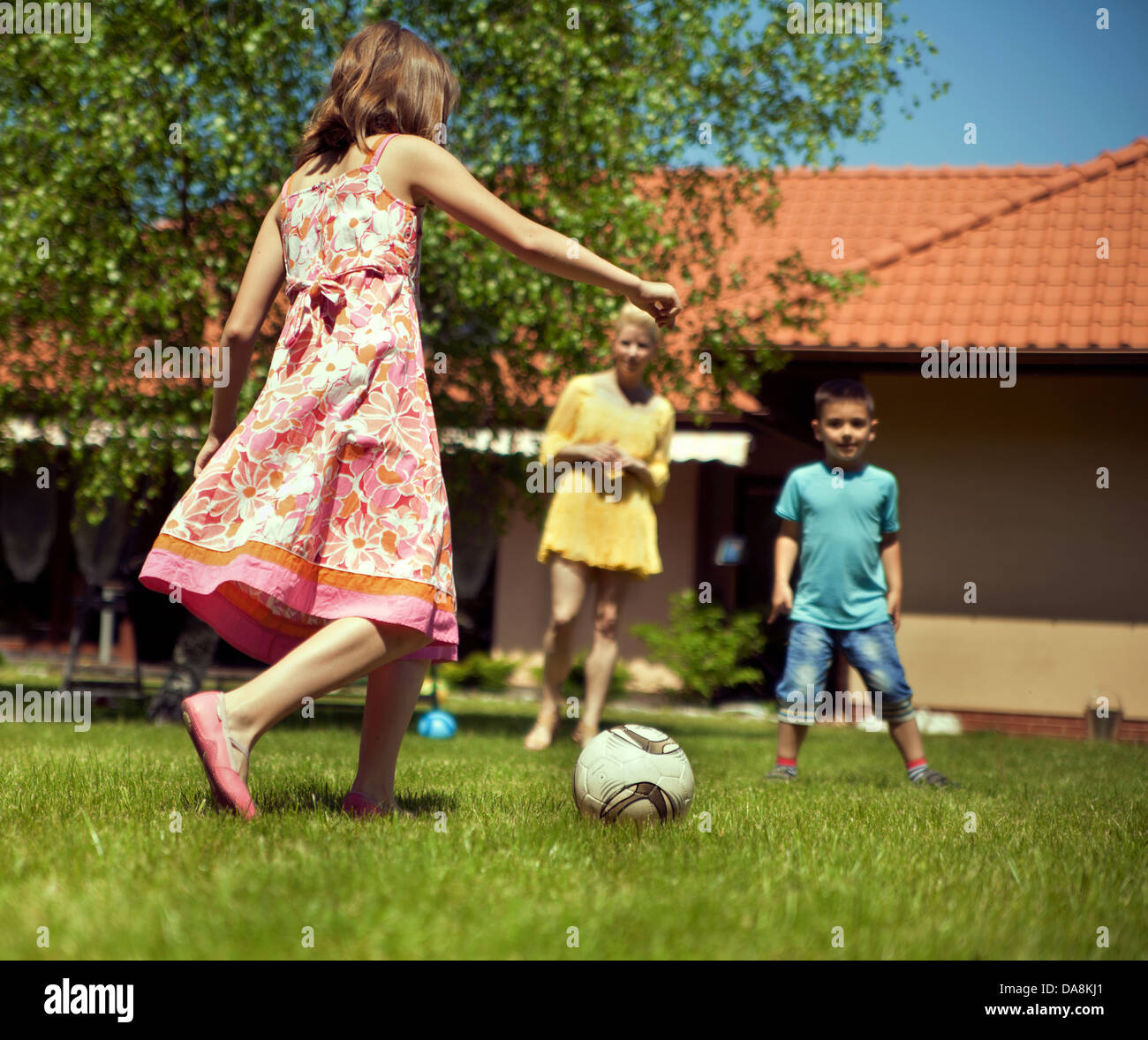 Happy family playing football in their garden - Stock Image