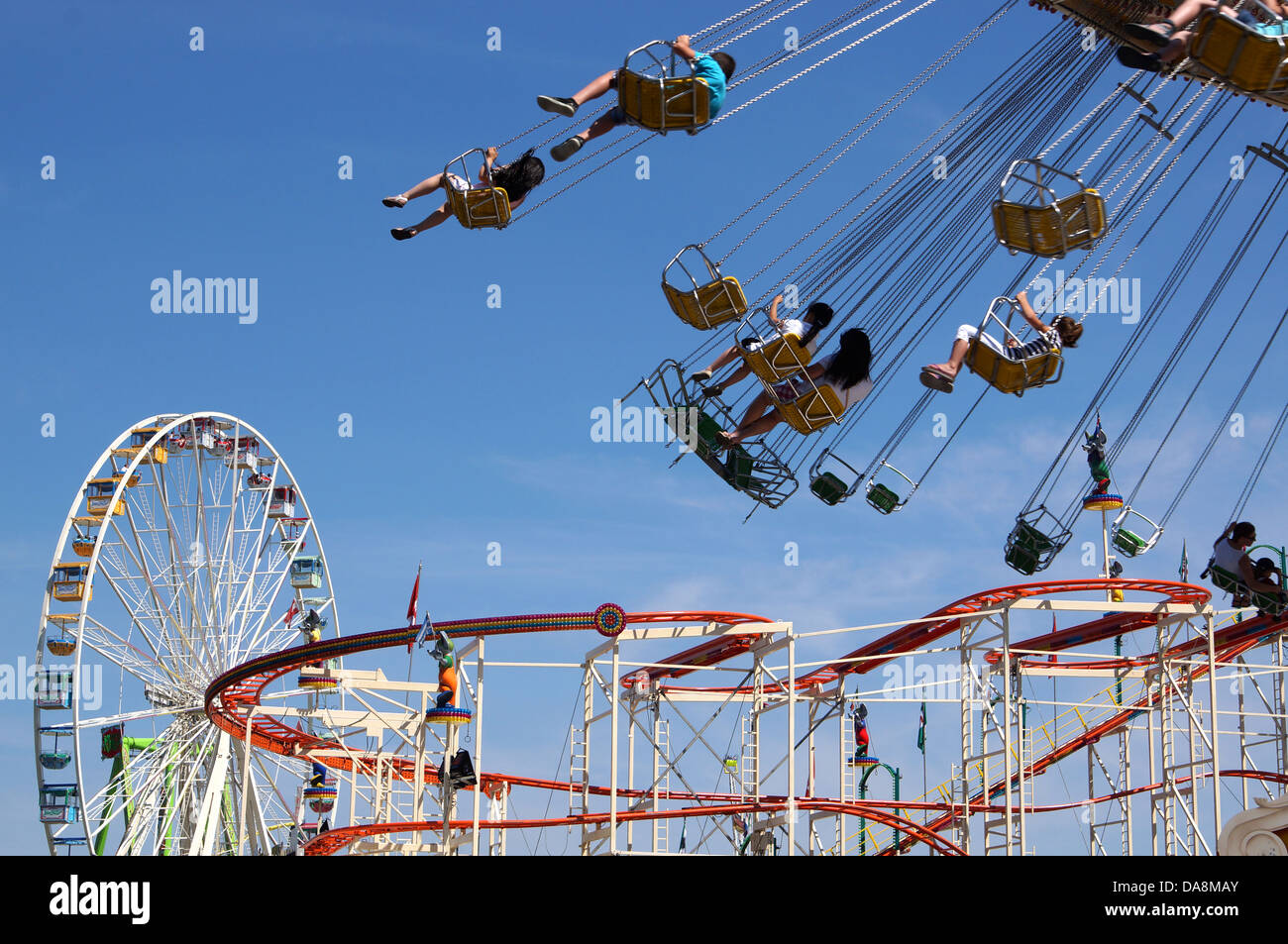 ferris wheel, roller coaster and chairoplane carousel at the annual Schuetzenfest fun fair in Hanover, Germany, - Stock Image
