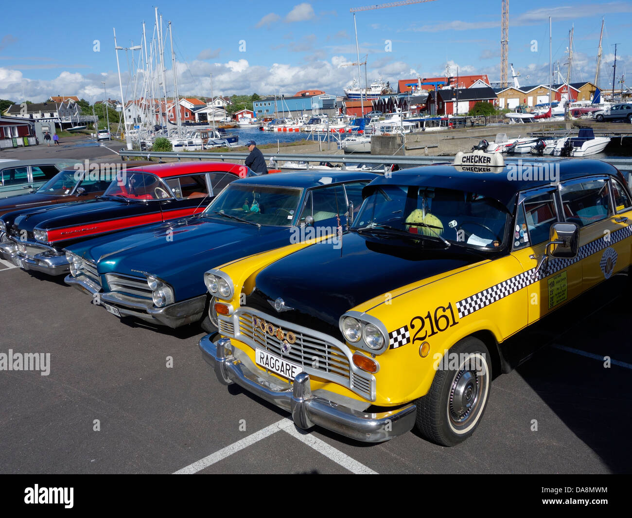 A retro Checker Taxicab and classic cars line up on a parking lot in a marina in Sweden. - Stock Image