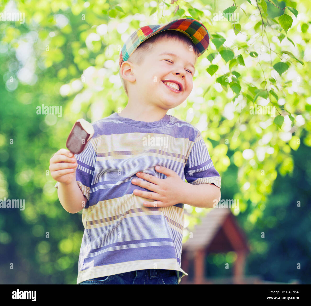 Contented small kid eating an ice cream - Stock Image