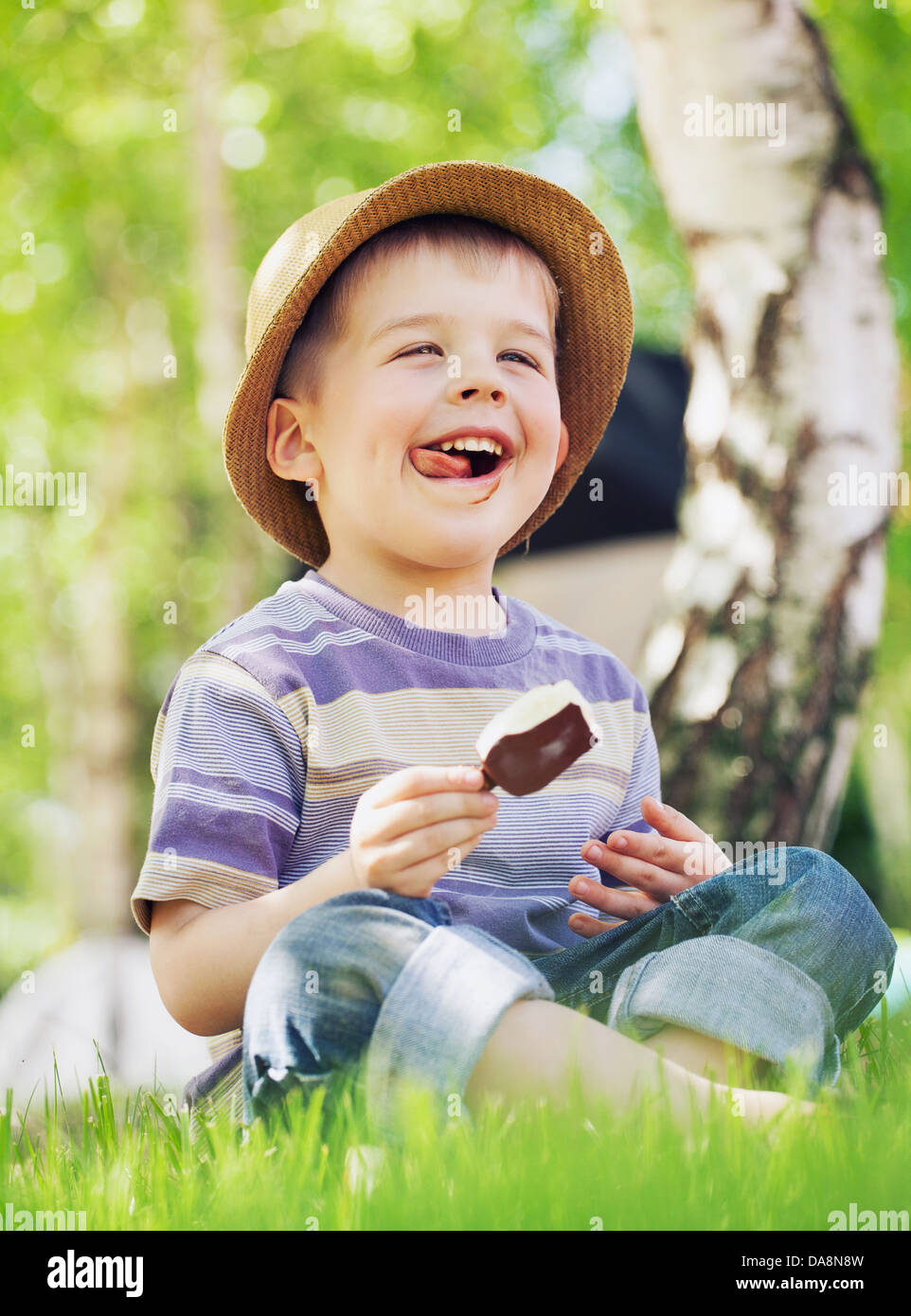 Satisfied little kid consuming an ice cream - Stock Image