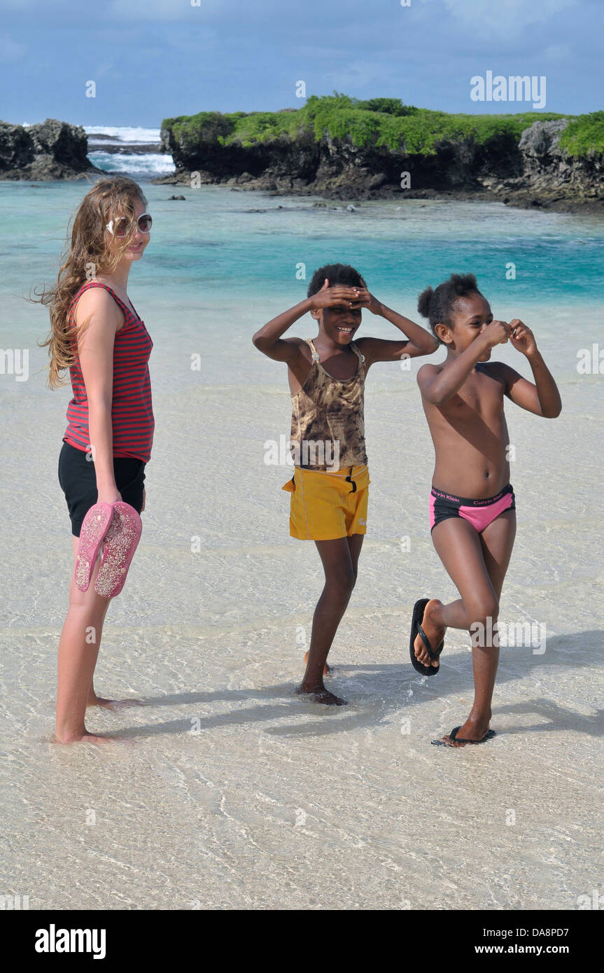 Two Vanuatu girls and tourist girl enjoy sunny beach with warm shallow water, coastal rocks and ocean in background - Stock Image